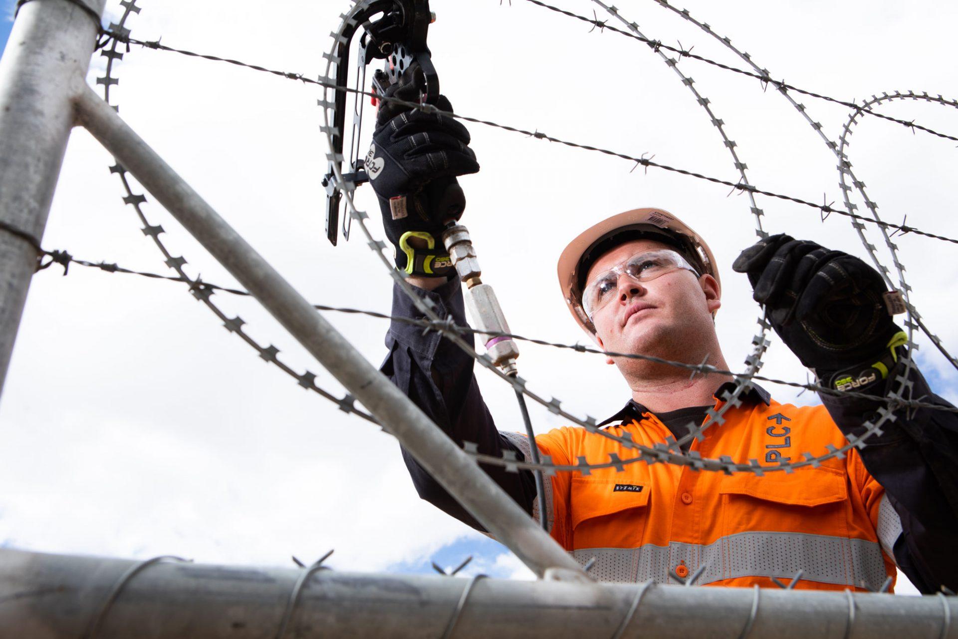 PLC worker installs security razor wire.